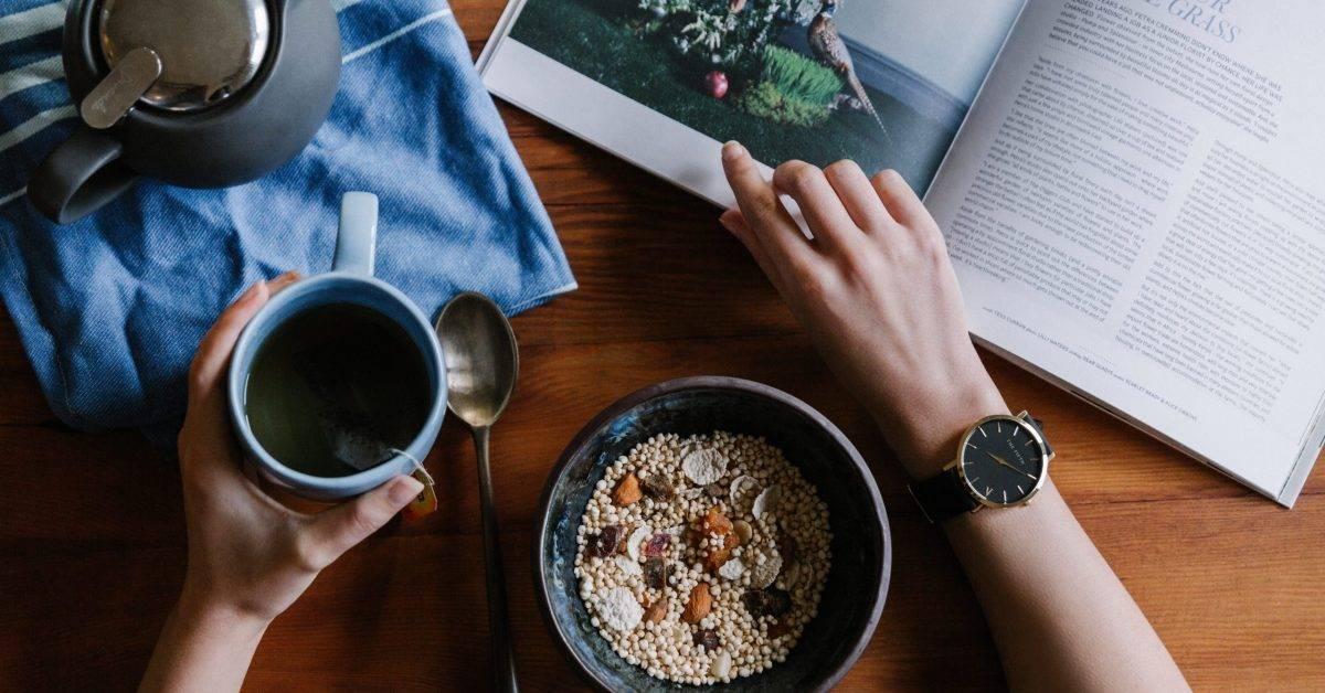 person holding blue ceramic mug and white magazine