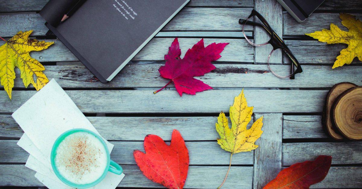 assorted-color leaves near eyeglasses, books, and green ceramic mug